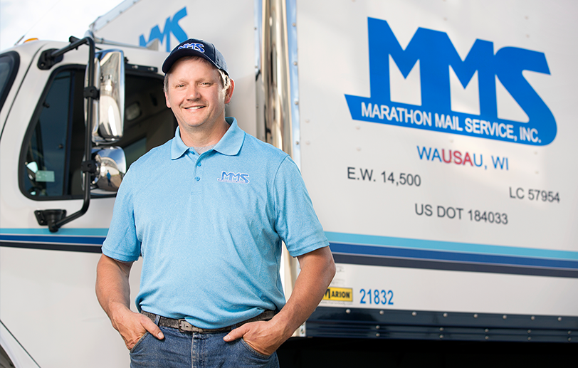 Marathon Mail representative standing in front of a truck