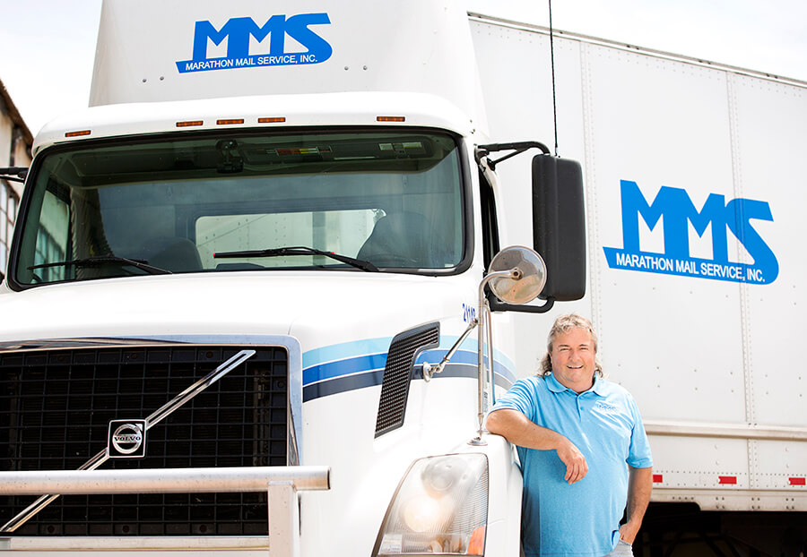 MMS Driver standing in front of a truck