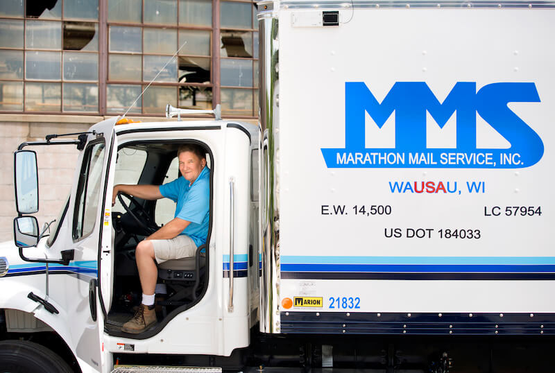 Man sits in the open cab of an MMS truck