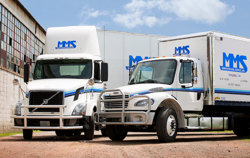 Two MMS Trucks in front of a warehouse